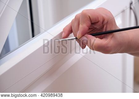 A Senior Woman Paints The Door Of A White Cabinet With A Brush. Painting To Restore Damaged Furnitur