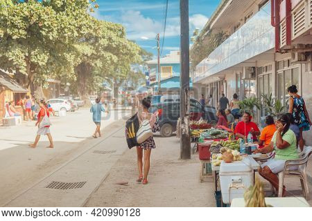 Fare, Huahine, French Polynesia - 4 FEBRUARY 2019- Travel tourist woman walking in street of Fare, French Polynesia during Huahine island cruise excursion going snorkeling on Tahiti holiday vacaton.