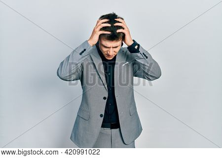 Young caucasian boy with ears dilation wearing business jacket suffering from headache desperate and stressed because pain and migraine. hands on head.