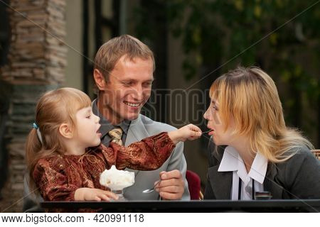 Happy family enjoying ice-cream in outdoors cafe