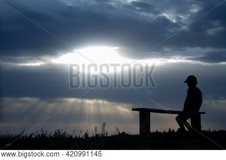 Rear View Of loneliness Boy Sitting On Bench While Looking At Sunset
