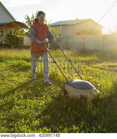woman in summer backyard mowing grass lawn mower
