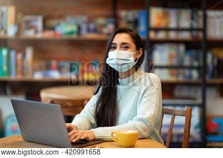Young Arab Woman In Mask Searching Job During Covid-19 Pandemic, Using Laptop In Cafe, Checking Vaca