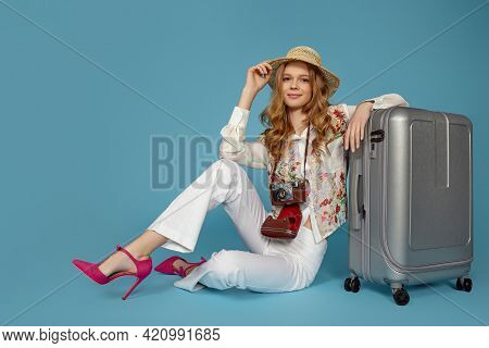 Happy Woman In Blouse And Trousers Sitting Near Suitcase