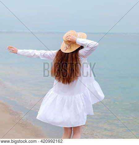 Silhouette Of Happy Enjoying Woman From Back With Thin Legs In White Beach Dress Having Rest At Suns