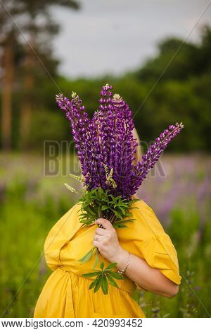 The Girl Covers Her Face With A Bouquet Of Lupine Flowers. A Girl In A Yellow Dress Collects A Bouqu