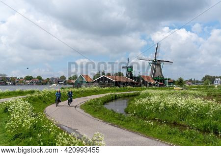 Dutch Senior Citizens Enjoy A Bicycle Ride Along The Canals Of North Holland With Traditional Windmi