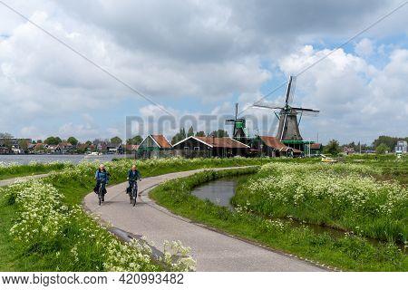 Zaandam, Netherlands - 18 May, 2021: Dutch Senior Citizens Enjoy A Bicycle Ride Along The Canals Of