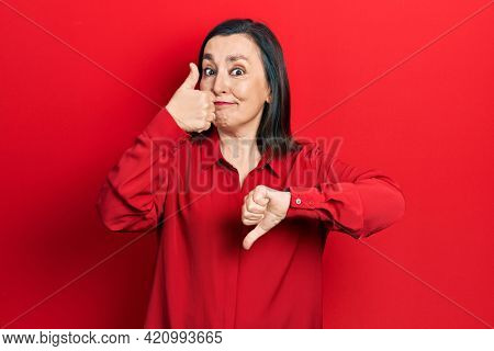 Middle age hispanic woman wearing casual clothes doing thumbs up and down, disagreement and agreement expression. crazy conflict