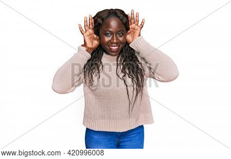 Young african woman wearing wool winter sweater trying to hear both hands on ear gesture, curious for gossip. hearing problem, deaf