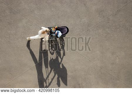 Woman With A Baby Stroller Crossing The City Street, Top View, Shadows On Asphalt. Concept Of Mother