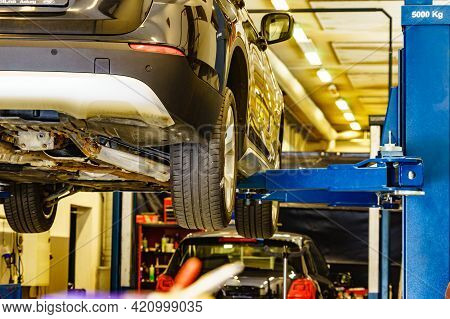 Car In Service. Auto Raised On Lift In Autoservice.