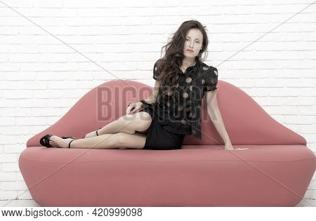 Confident And Sexy. Sexy Seductress. Glamorous Girl On Couch. Comfortable And Modern Furniture. Brun