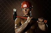 the beauty muscular worker chopper man with big heavy ax in hands tired appearance on netting fence background poster