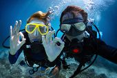 Underwater shoot of a young couple diving with scuba in a tropical sea and showing ok signal poster