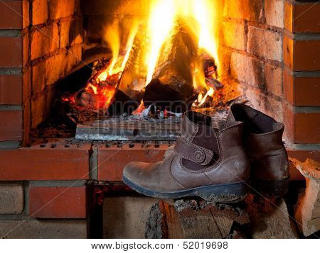 Boots Are Dried Near Fire In Fireplace