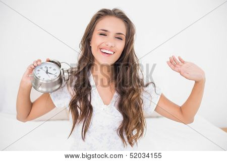 Smiling pretty brunette holding alarm clock in bright bedroom