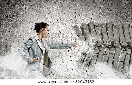 Image of businesswoman breaking bricks with hand