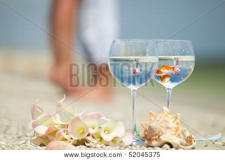 Reflection of holding bride and groom in wine glasses with golden fishes  poster