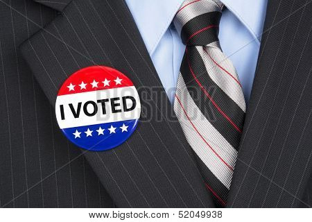 A male voter in his business suit wearing a vote pin on his lapel.