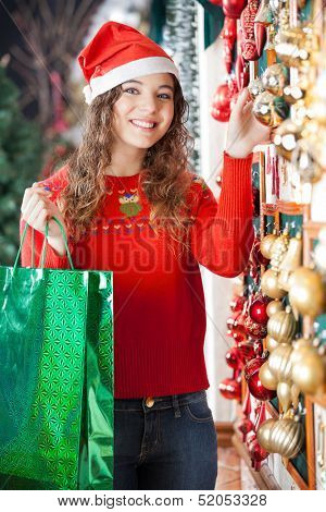 Portrait of beautiful woman in Santa hat with shopping bag buying Christmas ornaments at store