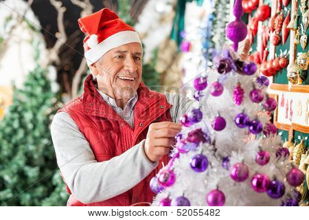 Happy male owner decorating Christmas tree with balls at store