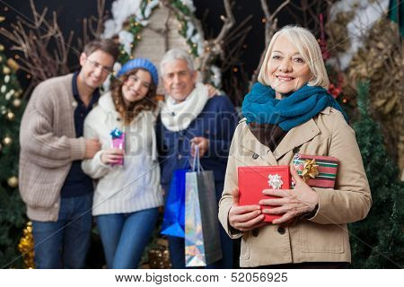 Portrait of happy senior woman holding Christmas presents with family standing in background at store
