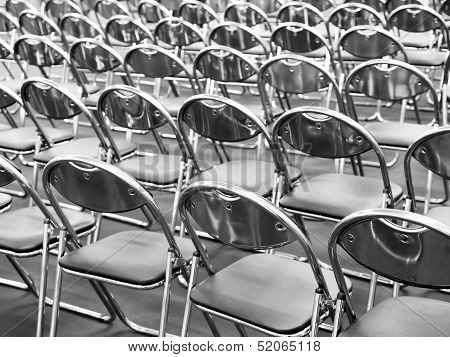 Rows of metal chairs at the conference in an empty room. Back view poster
