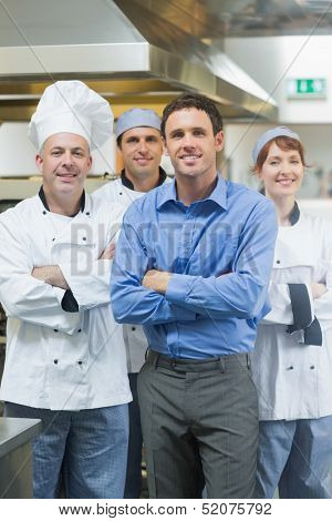 Handsome manager posing with some chefs in a kitchen