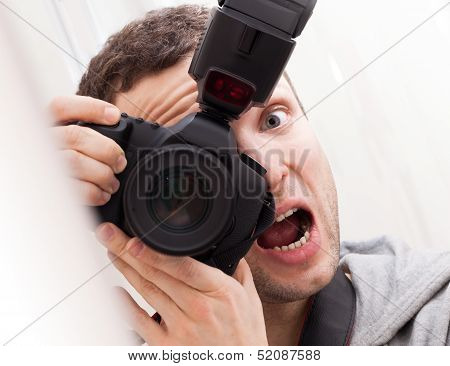 Portrait Of Fun Expressive Male Photographer With Camera On White Background