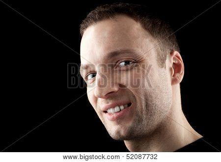 Young Caucasian Man Darkly Smirks. Close-up Portrait In The Dark