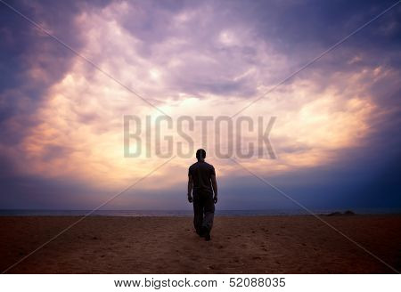 Man Goes To The Sea On Dark Sand Beach Under Beautiful Colorful Cloudy Sky