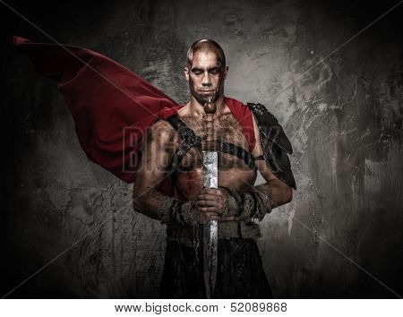 Wounded gladiator holding sword covered in blood with both hands poster