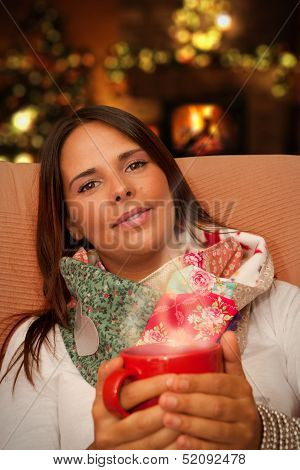 Woman Holding Hot Drink Seating Near Christmas Tree And Fireplace
