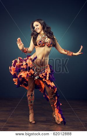 A dancing girl in the carnival costume. Belly dance