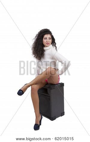 Gorgeous young female sitting on a audio speaker