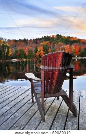 Wooden dock with chair on calm fall lake