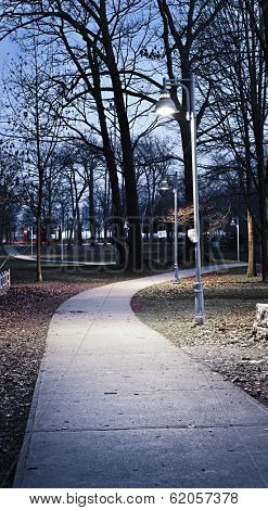 Path through city park at dusk with street lamps
