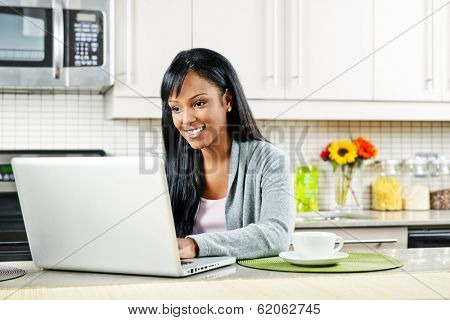 Smiling black woman using computer in modern kitchen interior
