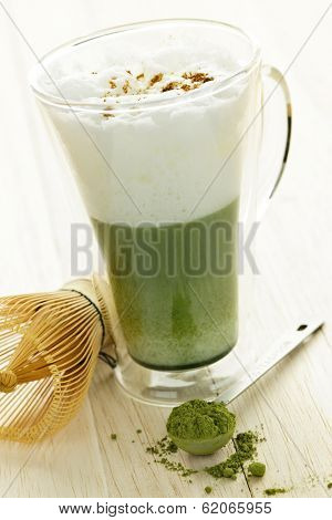 Matcha green tea latte beverage in glass mug with whisk