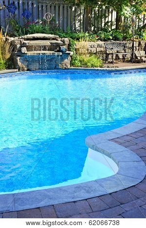 Outdoor inground residential private swimming pool with waterfall