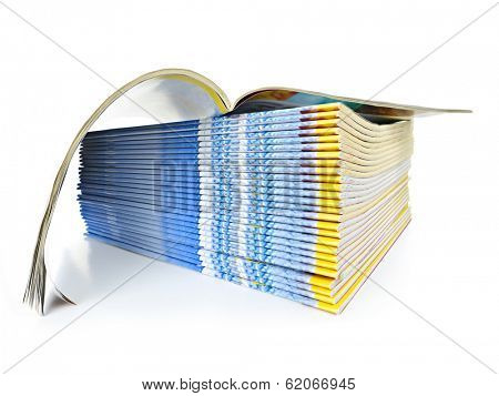 Many magazines stacked in a pile with one open isolated on white