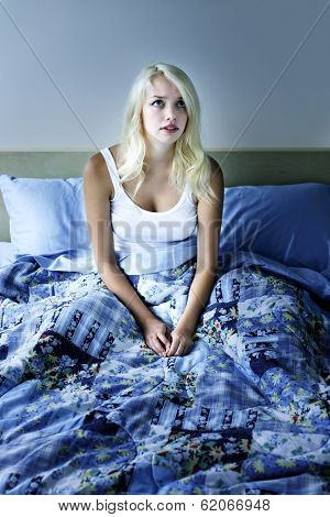 Sleepless woman sitting up in bed with insomnia