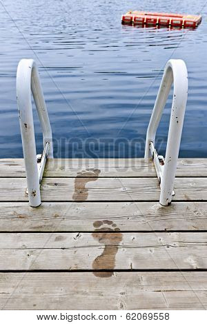 Wet footprints on dock with ladder and diving platform at calm summer lake in Ontario Canada
