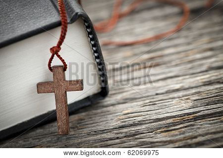 Closeup of wooden Christian cross necklace next to holy Bible poster