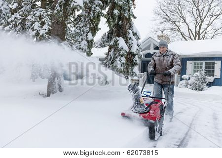 Man using snowblower to clear deep snow on driveway near residential house after heavy snowfall. poster