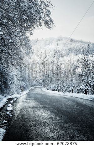 Icy winter road leading downhill through forest