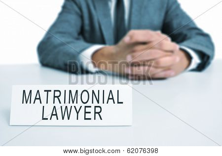 a man wearing a suit sitting in a desk with a desktop nameplate in front of him with the text matrimonial lawyer