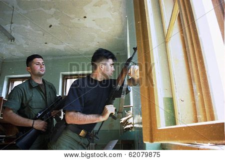 MOSTAR, BOSNIA, AUGUST 17: Bosnian Croat soldiers shoot at civilians from defensive positions in an apartment house during heavy fighting in Mostar, Bosnia, on August 17, 1993