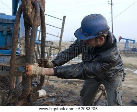 BAKU - AZERBAIJAN - JAN. 31: A roughneck grapples with a drilling rig in an oil production field near Baku, Azerbaijan, on Saturday, January 31, 2009.